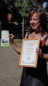 Die Vereinsvorsitzende Kristin Meier überreicht Frau Schwitters das erste Exemplar des neuesten Veranstaltungsflyers sowie eine Heimatvereins-Ehrenmitgliedsurkunde inklusive des freien Eintritts und stets einem Glas Sekt bei der Teilnahme an allen Veranstaltungen. Foto: Nicole Schimanski