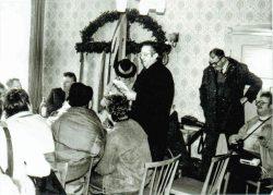 Hartmut Bock (rechts mit Fotoapparat und Tonbandgerät) dokumentiert eine Fastnachtsveranstaltung in Breitenfeld bei Klötze. Der altmärkische Heimatdichter  Fritz Hagen trägt gerade vor. Foto: Archiv Hartmut Bock
