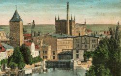 Bild 8 Mahlmühle (links) mit dem dahinter gelegenem hohen Speicher, dem Turbinenhaus und der Halbzeugmühle (rechts davon). Das erkennbare Windrad scheint wohl auf dem benachbarten Gefängnisgelände zu stehen. Sammlung Henry Bergmann.