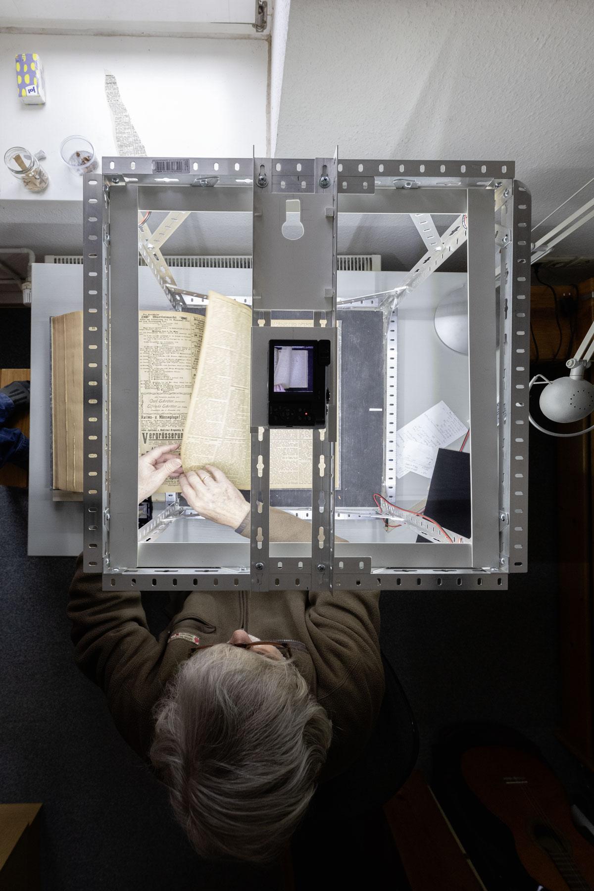 Die Zeitungsseiten sind behutsam anzufassen. Digitalisierung schützt sie vor dem Zefall durch Chlorfraß. Die Kamera wird vom Smartphone aus gesteuert. Foto: Matthias Behne